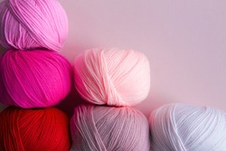 Columnarized acrylic yarn on a pink  background. A graph in the form of a nuanced gradient. The balls of yarn are located diagonally in the lower left corner.