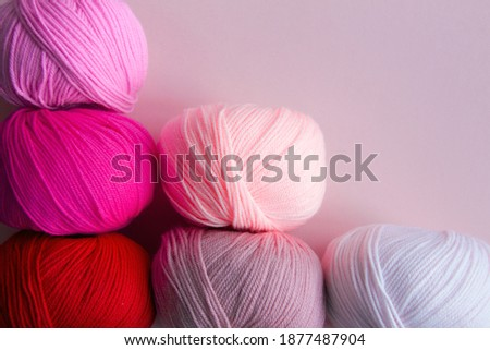 Columnarized acrylic yarn on a pink  background. A graph in the form of a nuanced gradient. The balls of yarn are located diagonally in the lower left corner. Photo stock ©