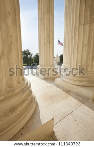 Columns of Supreme Court building frame an American flag in Washington DC - stock photo