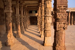 Columns with stone carving in courtyard of Quwwat-Ul-Islam mosque, Qutub Minar complex, Delhi, India