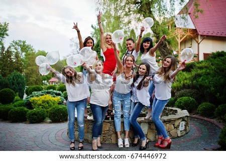 Comany of young women posing outside with inflated condoms at bachelorette party. #674446972