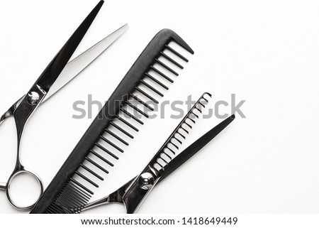 Comb and hair cutting shears, two pair texturizing or thinning scissors for haircut, professional salon equipment. Copy space, flat lay