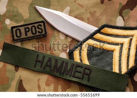 Combat knife and patches on multicam background
