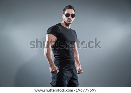 Combat muscled action hero man wearing black t-shirt with pants and sunglasses. Studio shot against grey.