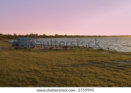 combi van or campervan / rv on the edge of the lake at sunset