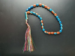 Combination of two colors Tasbih or prayer beads for Muslim. Also known as misbaha. Used as a counter for repetitions of prayers or other ritual recitations. Blue and orange. Black background.