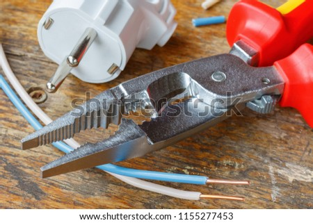 Combination pliers for wiring with electrical plug and copper wires on wooden table in workshop