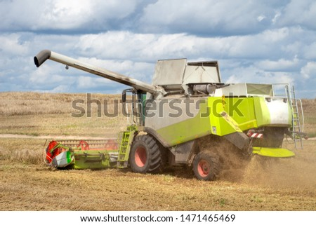Combine harvester on wheat field harvesting grain. Agricultural scene. Harvest time #1471465469