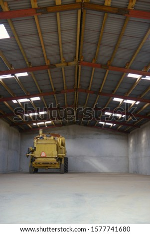 combine harvester standing ready for harvest in a warehouse