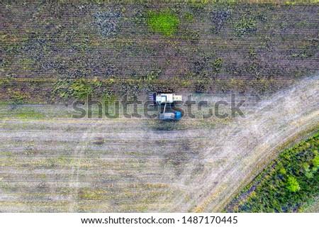 Combine harvester uploads harvest sunflower grains to dump truck. Harvesting season. Agriculture scene. Agricultural harvest field