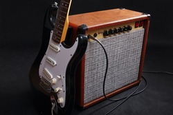 Combo amplifier for electric guitar with black guitar on the black background.