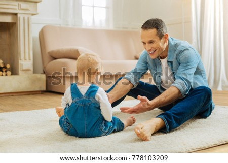 Come here. Cute positive attentive father looking at his lovely little child and approaching him while sitting on the floor in a light room #778103209