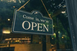 COME IN, WE ARE OPEN - Open sign broad hang on entrance door with copy space at coffee shop or restaurant