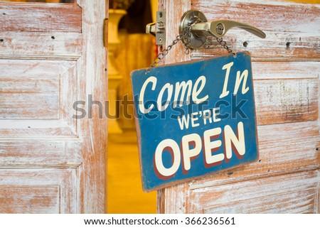 Come In We're Open on the wooden door open