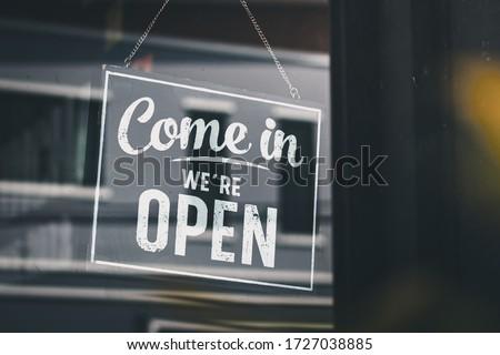Come in we're open, vintage black retro sign in glass door storefront Photo stock ©