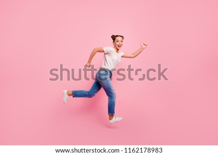 Come on, race! Full legs, body, size portrait of cute and lovely happy brunette girl who runs through the air in a white T-shirt and blue jeans isolated on vivid pink background