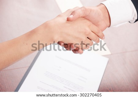 Come to agreement. Close up of nice colleagues shaking hands with document lying on the table in background