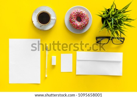 Come up with brand identity. Blank stationery for branding near coffee and donut on yellow background top view mockup pattern