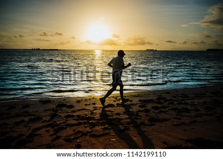 Comece o dia com uma boa corrida na praia. Foto stock ©