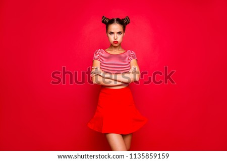 Comedian humor joke concept. Portrait of grimacing funny capricious young woman model with bun hairstyle holding air in cheeks isolated on red background