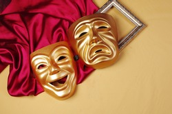 Comedy and tragedy masks with purple drapery.