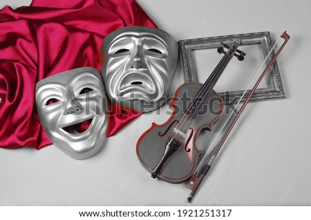 Comedy and tragedy masks with purple drapery, violin and bow on a light background. Theater symbol. Stockfoto ©