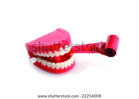 Comedy wind-up chattering teeth biting party blower isolated on white with clipping path