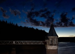 Comet Neowise above the pumping house of a large reservoir in the Brecon Beacons