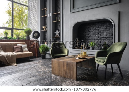 Comfort armchairs near wooden table against decorative fireplace, couch, houseplants and home decor in fancy apartment. Elegant living room with stylish and loft interior design