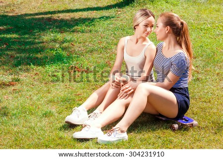 Comfort of solitude. Portrait of two young attractive lesbian women sitting on skate board in park and flirting.