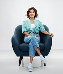 comfort, people and furniture concept - portrait of happy smiling young woman in turquoise shirt and jeans sitting in modern armchair over grey background