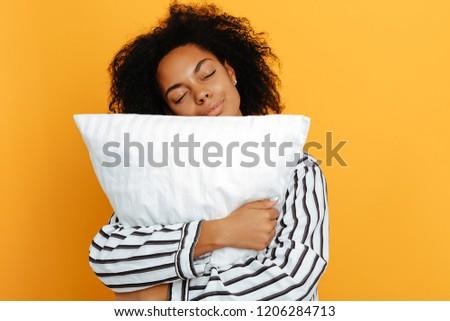 Comfort Sleeping. Dreams. Woman portrait. Afro American girl in pajama is bonding a pillow, on a yellow background