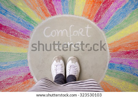Comfort zone concept - Feet standing inside comfort zone circle surrounded by rainbow stripes painted with chalk on the ground