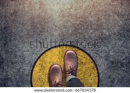Comfort Zone concept, Male with leather shoes steps over circle line to outside bound, Top view and Dark tone, Grunge Dirty Concrete Floor as Background