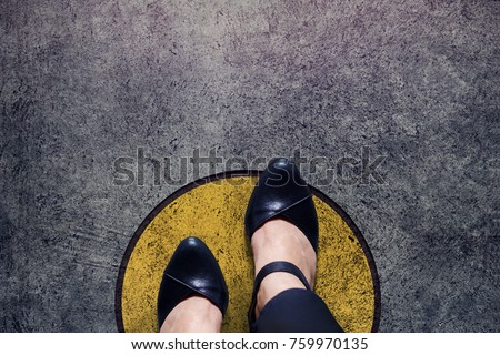 Comfort Zone concept, Woman with leather shoes Steps over circle line to outside bound, Top view and Dark tone, Grunge Dirty Concrete Floor as Background