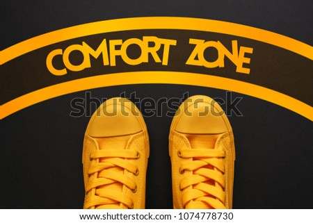Comfort zone concept, young adult person in yellow sneakers standing inside of the circle, top view