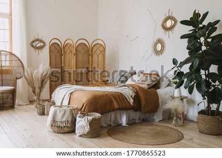 Comfortable apartment in bohemian style interior with hygge bedroom, pillow and bedspread on bed, bamboo dressing screen, home decor, dry plants in vase, wicker basket, houseplant on floor