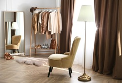 Comfortable armchair and rack near window with stylish curtains in room. Interior design