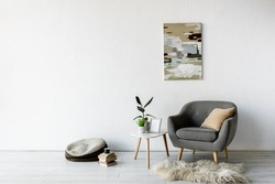 comfortable armchair near coffee table with green plants, frame and painting on wall in modern living room