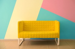 Comfortable armchair near color wall