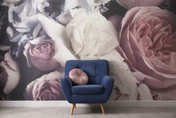 Comfortable armchair near wall with floral wallpaper. Stylish living room interior