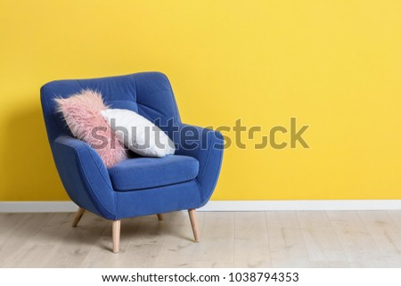 Comfortable armchair with soft pillows near color wall