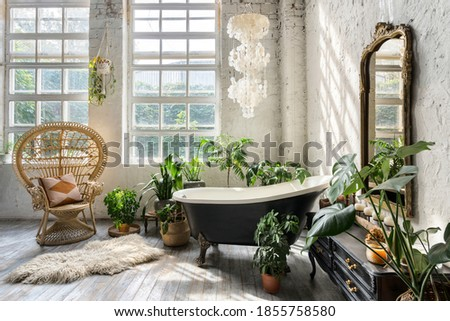Comfortable bathroom with interior design in boho chic style, bathtub, vintage commode with mirror, wicker armchair, fluffy carpet and green houseplants in flowerpots