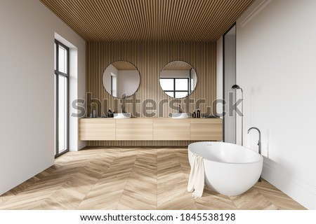 Comfortable bathtub and sink standing in modern bathroom with white and wooden walls and wooden floor. 3d rendering