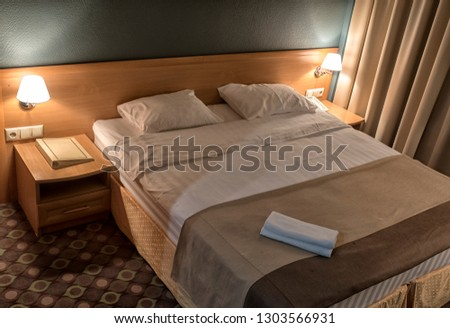 comfortable bed in the hotel room. Top view of white bedding sheets and pillow.  #1303566931