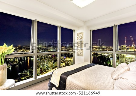 Comfortable bed near city view at night, stylish bedroom including abstract designs also town area can see through the window, luxurious look from attractive lamps near the glass panel.