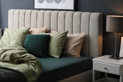 Comfortable bed with new pistachio linens in modern room interior