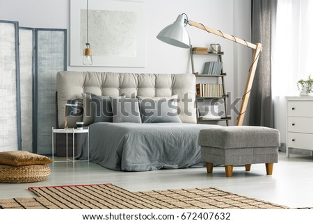 Comfortable bed with quilted headboard and grey pillows #672407632