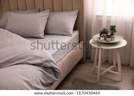 Comfortable bed with soft blanket near window indoors Photo stock ©