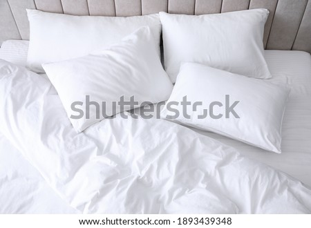 Comfortable bed with soft white pillows, closeup
